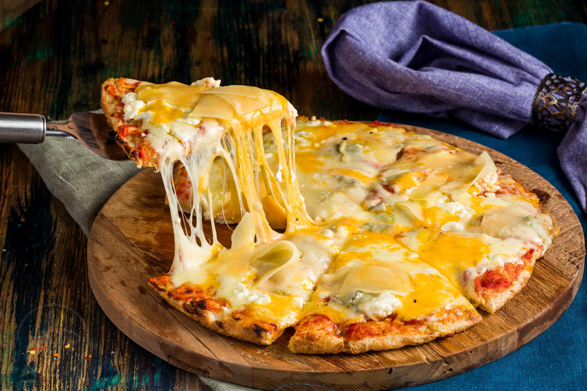 Pizza pe un blat de lemn cu o felie trasa din ea